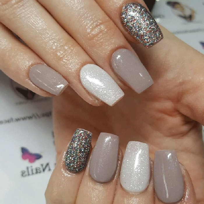 pearlescent nail polish, in silver and beige, on eight coffin shaped nails, nude nails with glitter in different colors