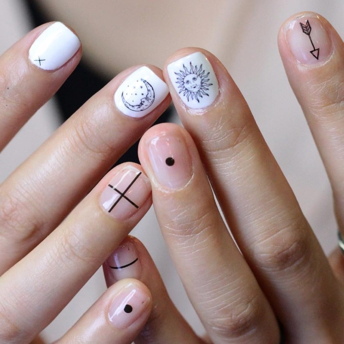 stickers depicting, sun and moon, arrow and crossing lines, dot and stripe, on short nude, and white nails