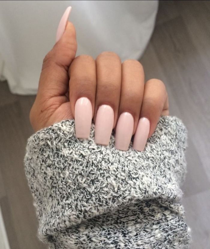 light candy pink, nude gel nails, with long ballerina slipper shape, on a hand, holding a slat and pepper knitted sleeve