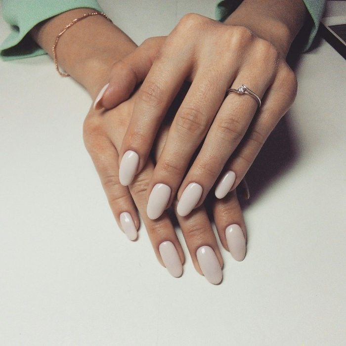 ivory colored nails, with an oval shape, on two hands, one resting on top of the other