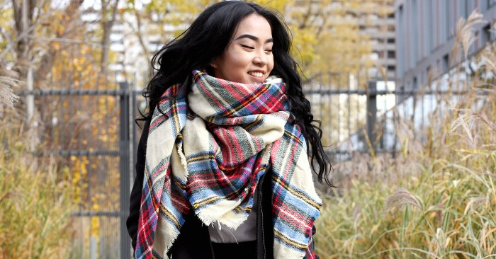 east asian woman, with black wavy hair, smiling while wearing an oversized, plaid scarf in white, and blue, red and grey, how to wear a square scarf