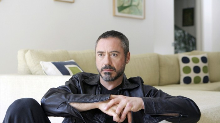contemporary photo of robert downey jr, dressed in black, and wearing a very short, buzzed haircut with grey areas