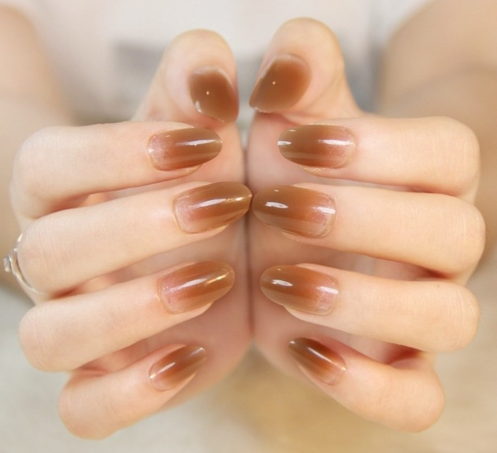 beige ombre-effect nail tips, decorating an oval manicure, with best nude nail polish, on two pale hands