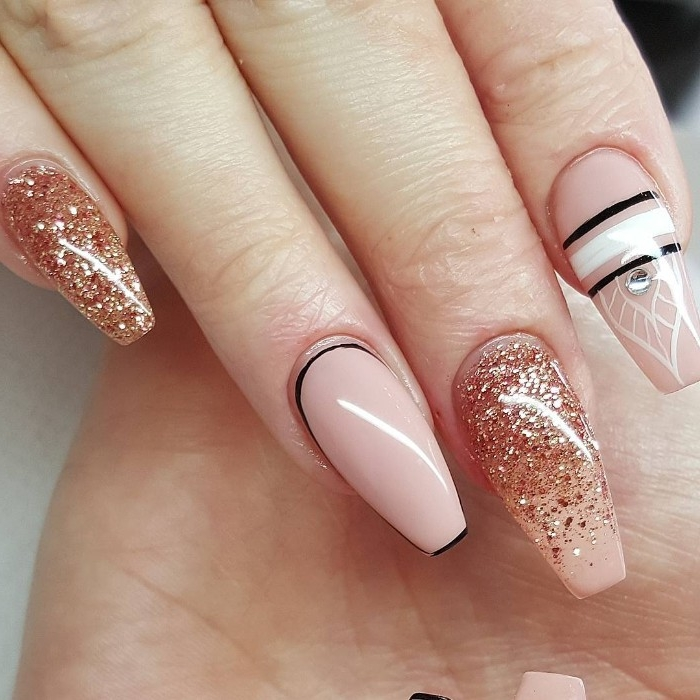 nude nail designs, long coffin shaped manicure, in nude pink, decorated with rose gold glitter, white and black stripes, and a silver gem sticker