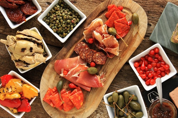 selection of easy appetizers for a crowd, wooden board with prosciutto and salami, dishes with vegetables