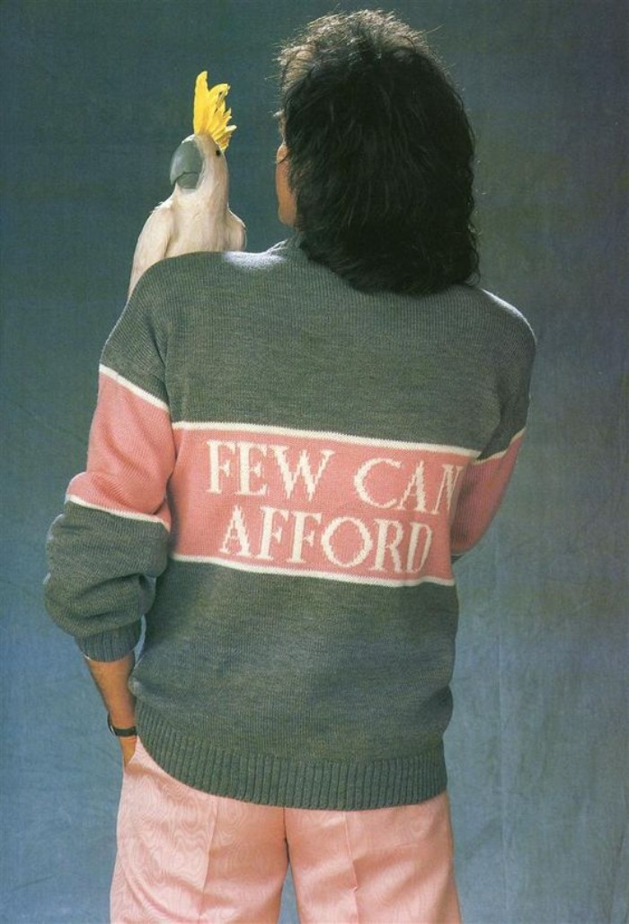 view from the back of a man, with medium length black wavy hair, holding a parrot doll on his shoulder, and dressed in a grey, pink and white sweater, with an inscription saying, few can afford, 80s outfits guys