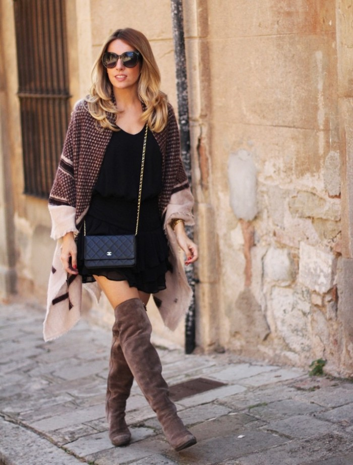 mink colored suede over the knee boots, paired up with a black mini dress, and accessorized with a patterned, ivory and dark grey blanket shawl, worn like a cardigan