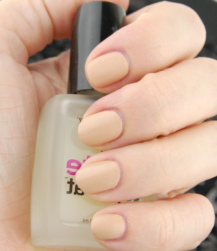 creamy peach colored nail polish, on four short oval nails, attached to a pale hand, holding a bottle of nail polish