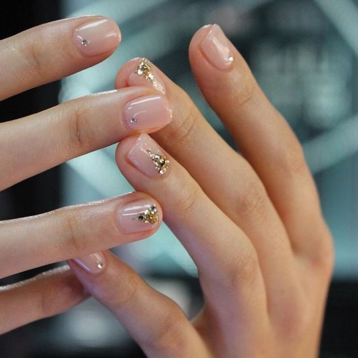 small gem nail decal stickers, in silver and gold, on the short, square nails of two hands,