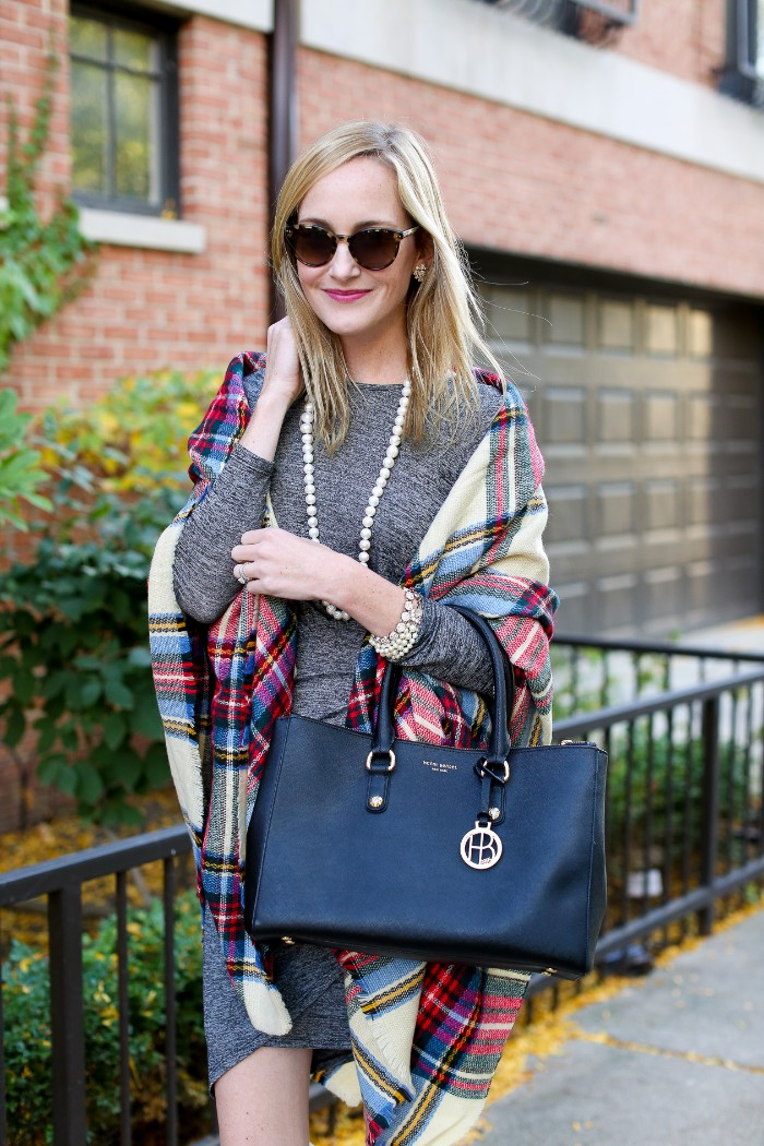 blonde woman with sunglasses, wearing a grey jumper dress, and a pearl necklace, and holding a black designer bag, how to wear a blanket scarf