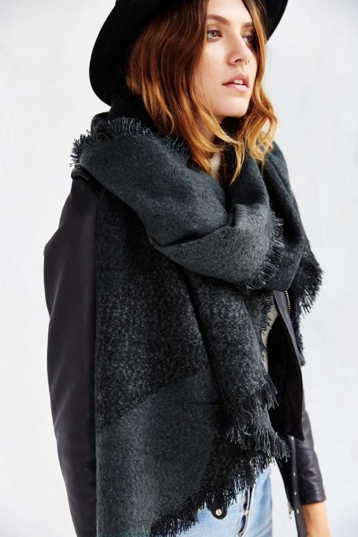 charcoal grey oversized scarf, combined with a black felt hat, black leather jacket, and pale denim jeans, scarf outfits, worn by a young woman, with wavy shoulder length hair