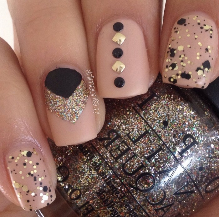 multicolored and gold glitter, stickers and splashes of black nail polish, decorating short and square, nude matte nails