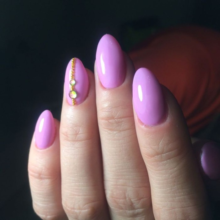 iridescent and gold rhinestones, on the ring finger nail, of a pale hand with short pointy nails, and pink manicure