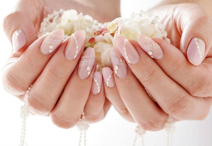 wedding manicure idea, oval nails painted in nude pink, and decorated with pearl-like, white nail decal stickers, on two hands, holding flower petals