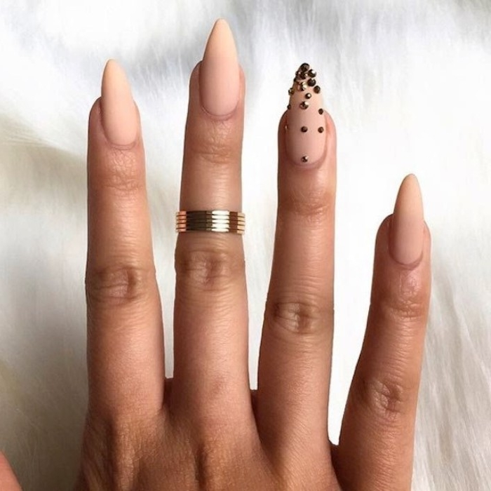 bead-like metallic nail decal stickers, decorating one of four, nude matte nails, on a hand with a gold ring