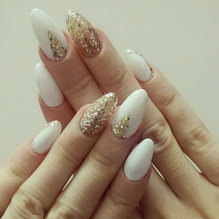 long oval nails, in white and gold, decorated with large glitter flakes, and seen in close up, on a white background