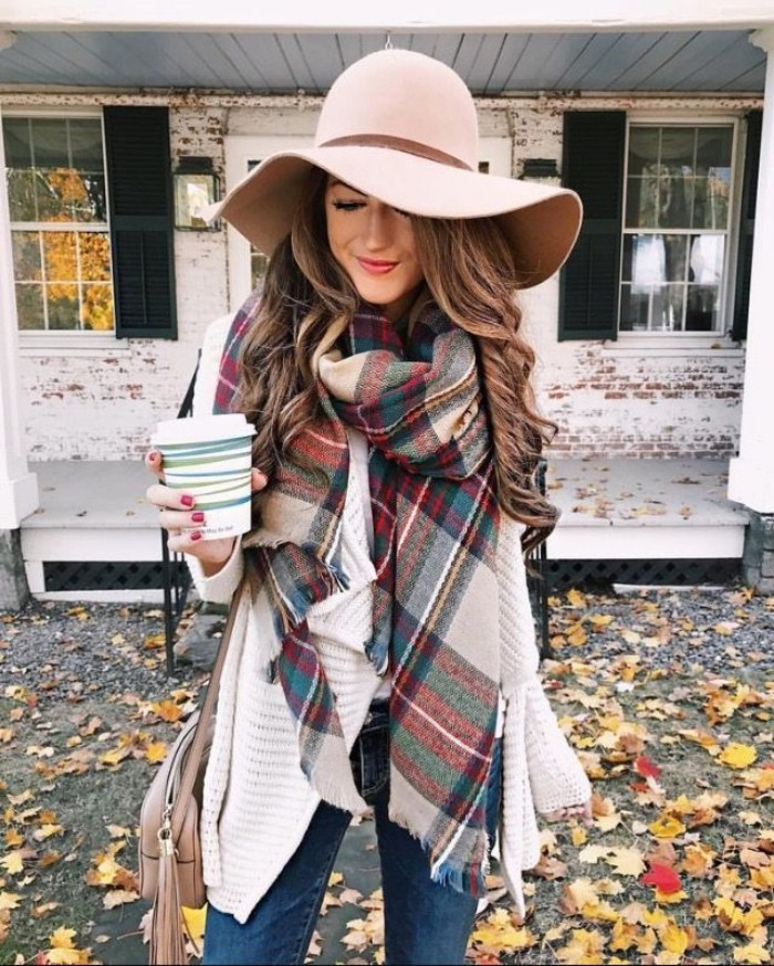felt hat in pale powder pink, worn by a smiling brunette woman, with curled hair, with jeands and a white cardigan, wrapped in a plaid scarf, and holding a paper coffee cup