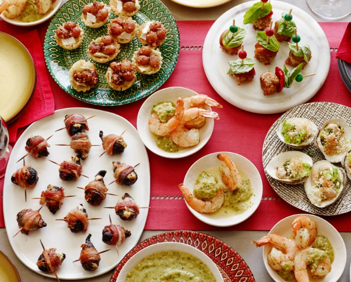 several plates filled with hor dorves, savory tartlets with vegetables, prawns and mussels, bacon-wrapped olives and more