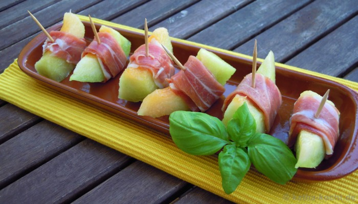 melon pieces wrapped in prosciutto, hor dorves, inside a brown oval plate, decorated with a sprig of fresh basil