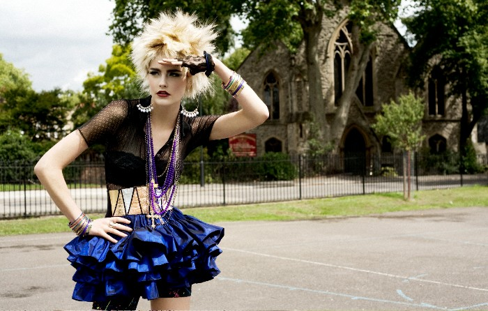 slim blonde woman, dressed like a punk rocker, short spiky hair, 80s clothes, shiny blue rara skirt, sheer black top, lots of jewelry