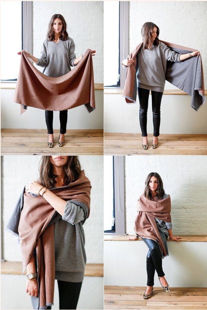 demonstration on how to wrap a blanket scarf, in four images, brunette woman black leggings, and a pale grey jumper, folding a brown and grey reversable shawl, around her shoulders