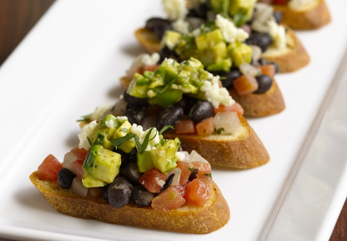 ceramic plate in white, containing five pieces of bruchetta, topped with chopped tomatoes and avocado, cheese and olives