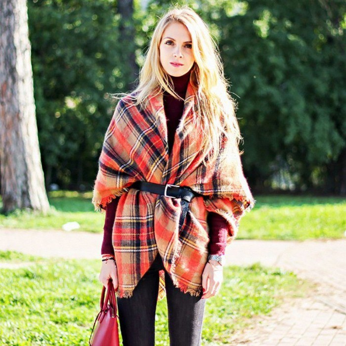 belt made from black leather, securing a red tartan oversized scarf, worn by a blonde woman, in a wine red jumper, and dark skinny jeans