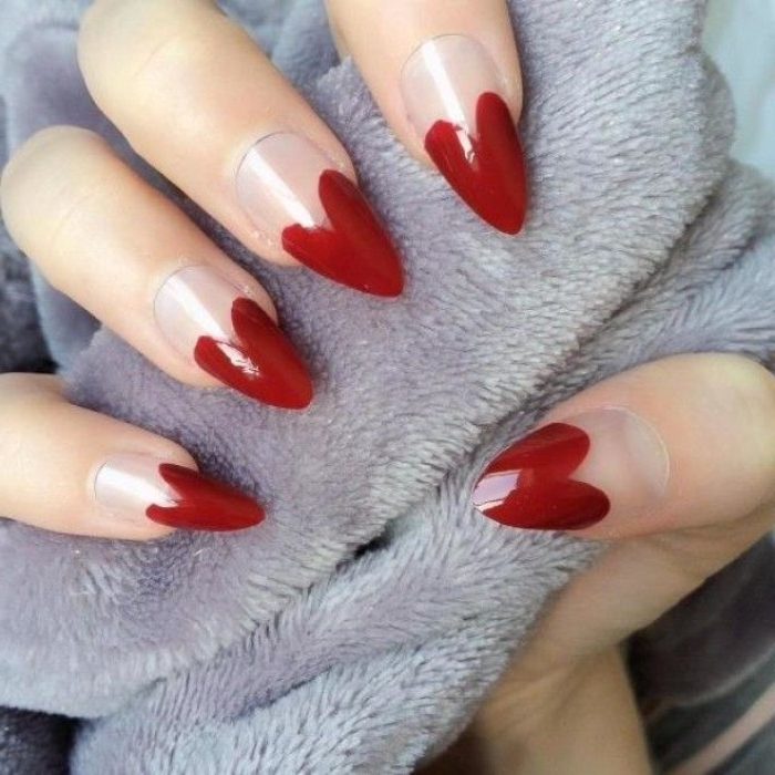 heart shapes painted in dark red, on the tips of a long, pointy manicure, with clear nude nail polish, on a hand, holding light grey fabric