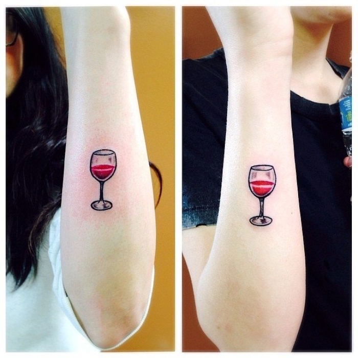 glasses half-filled with red wine, identical tattos for firends, done with red and black ink, on the lower part, of two pale arms