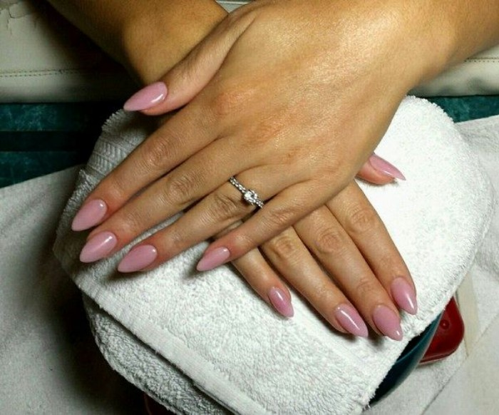 diamond ring on one of two hands, both resting on a white towel, with an almond manicure, painted in a pale pink nail polish