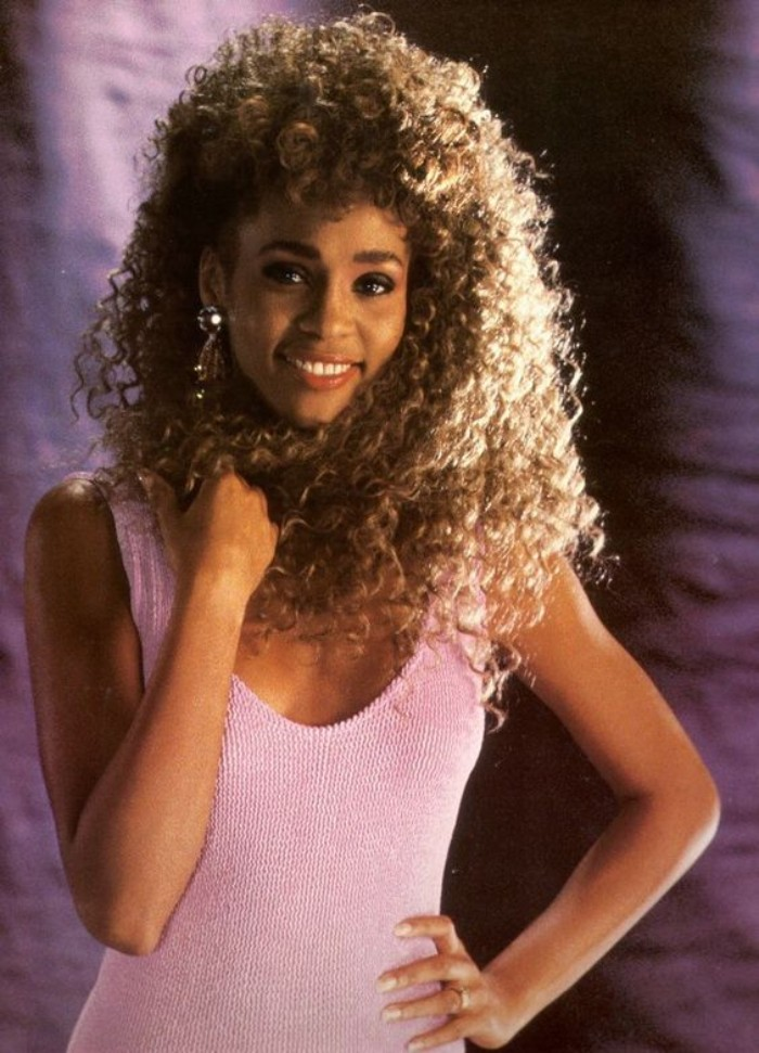 pastel pink tank top, worn by smiling young whitney houston, with long and voluminous, brunette curly hair