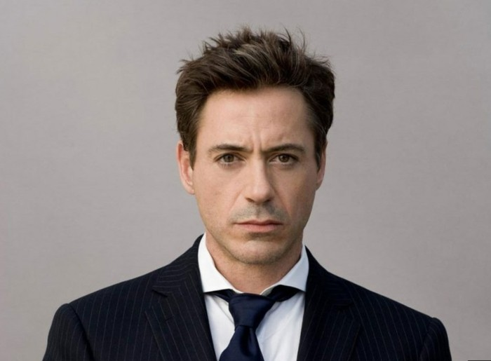 a younger robert downey jr, dressed in a pinstripe suit, with a white shirt, and a black tie, wearing a short, brunette crew cut