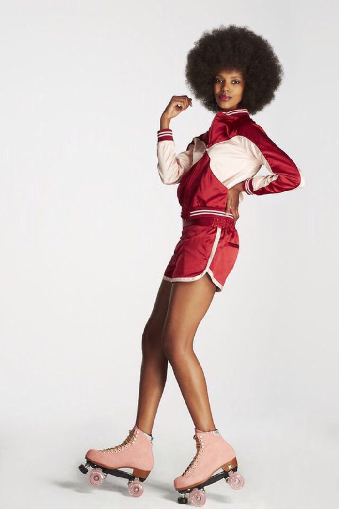 afro hairdo, worn by a black woman, dressed in a shiny, red and white tracksuit top, with matching shorts, 80s outfits, pink roller skates