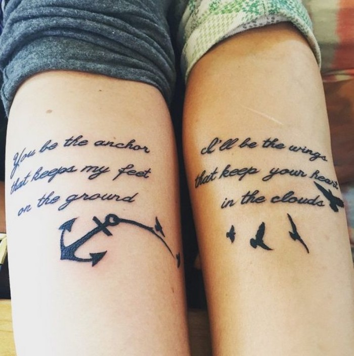 romantic messages done in black ink, near the nooks of the elbows of two arms, placed next to each other, matching couple tattoos, one features an anchor, and the other birds in flight