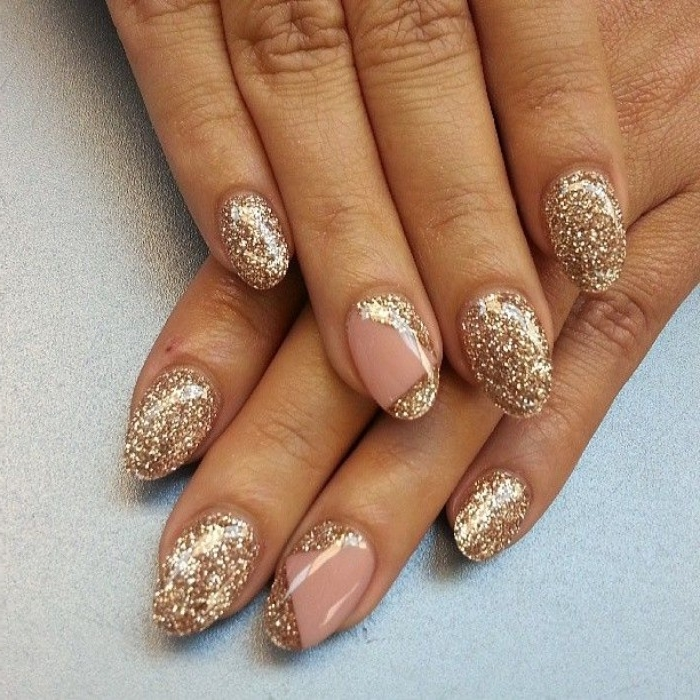 tan hands with oval manicure, featuring pink nude nails, almost entirely covered in gold glitter