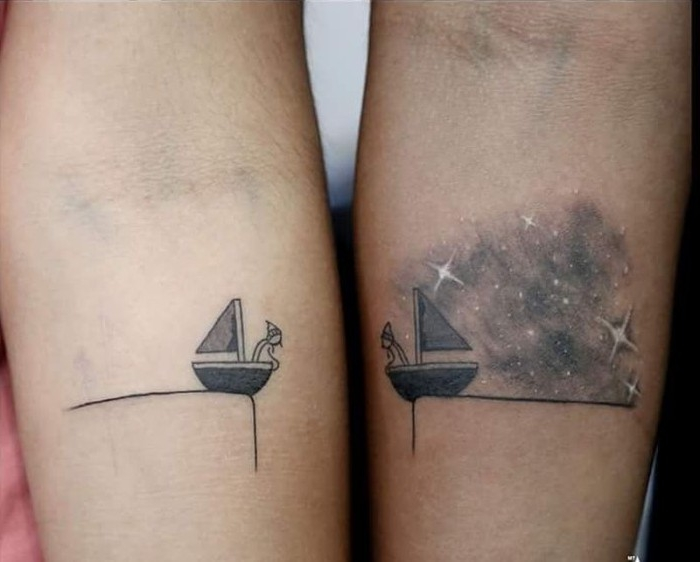 stick figures in two sailing boats, tattooed under the nooks of the elbows of two arms, matching friend tattoos, one has a starry sky in the background