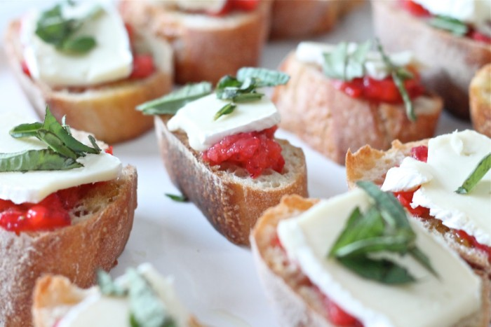 simple bruschetta with salsa, brie and fresh basil leaves, on a white surface, seen in a close up