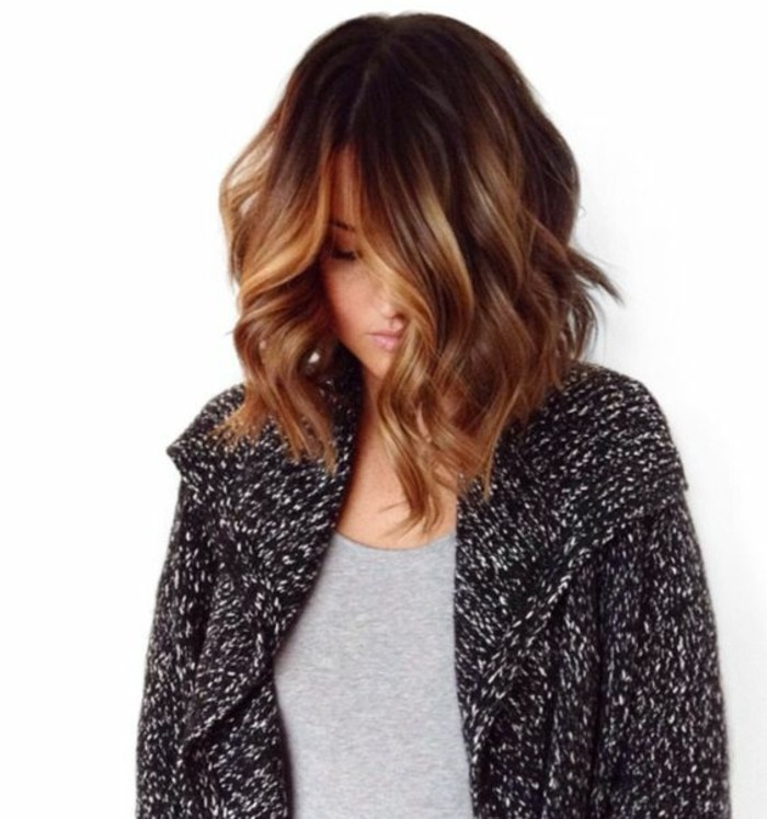 soft shoulder length hair, with loose curls and side part, featuring a caramel bayalage, on a young woman, in pale grey top, and salt and pepper cardigan