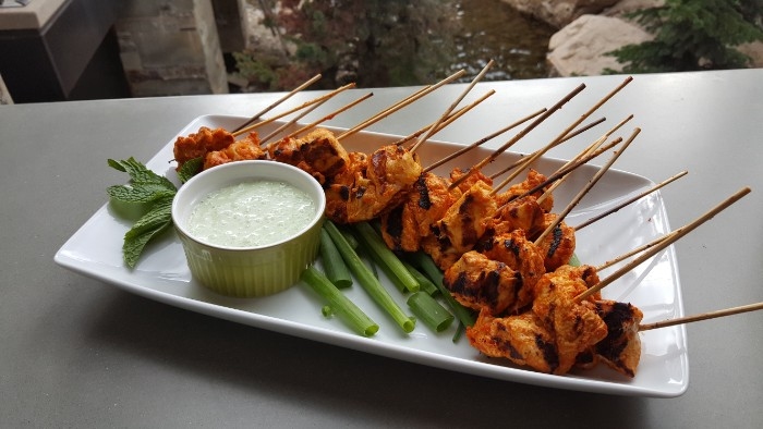 hour derves, grilled chicken skewers, on a white rectangular plate, near spring onions, fresh mint leaves, and a bowl with yoghurt dip