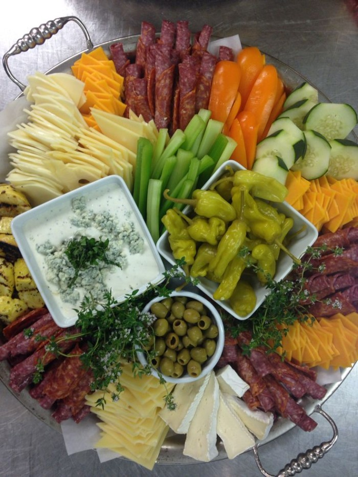 metal tray with a selection of hor dorves, different kinds of cheese and salami, jalapenos and pitted olives, chopped vegetables and yoghurt dip
