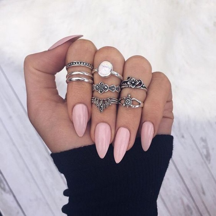boho-style silver rings, on a hand wearing a black sleeve, and long pointy oval nails, in pale pink,