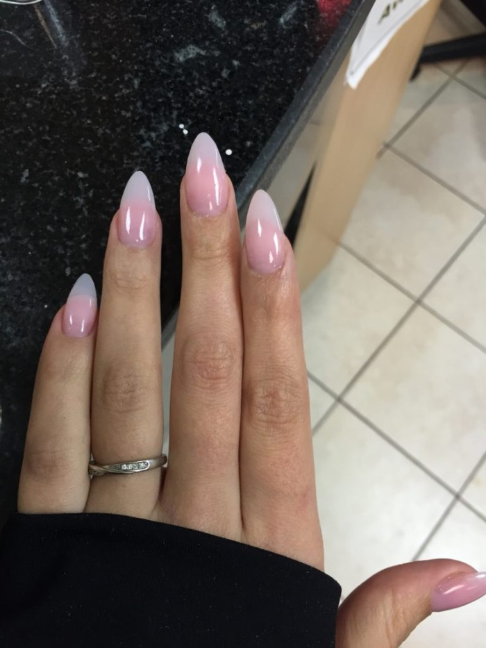 slender fingers with a long manicure, featuring sharp french tips, example of almond nail designs, on a hand in a black sleeve