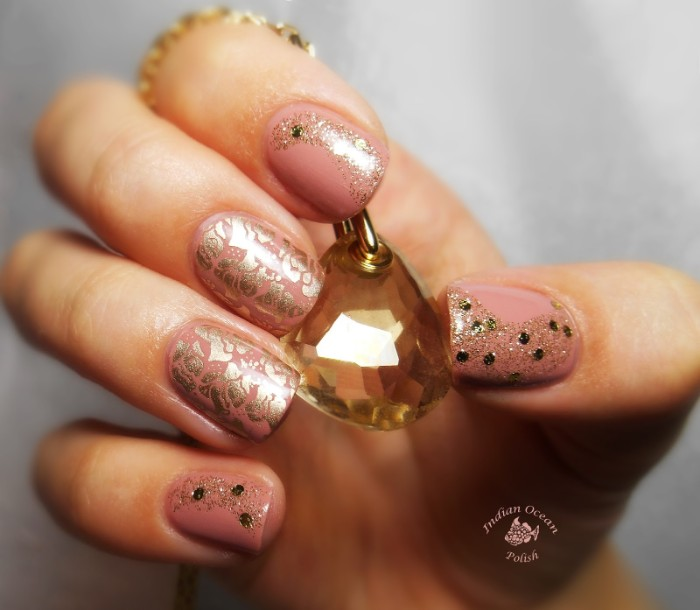 shimmering metallic motifs, fine gold glitter, and black decorative flakes, on top of a manicure, with nude nail polish, hand holding a crystal pendant