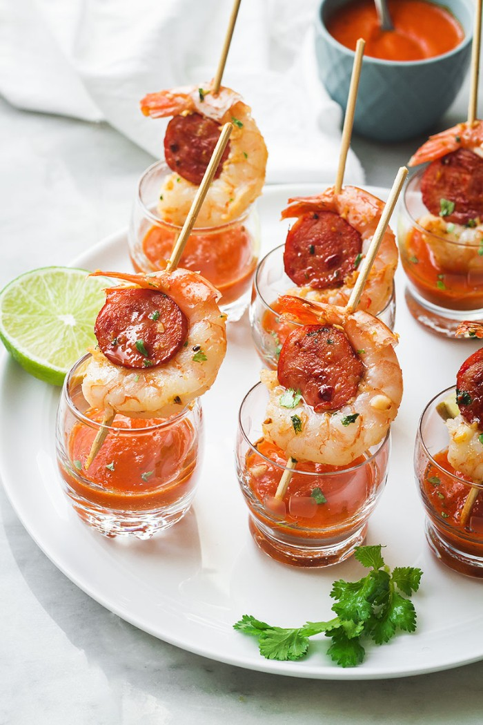 shot glasses containing an orange sauce, and skewers with prawns and chorizo, hor dourves on a white round plate