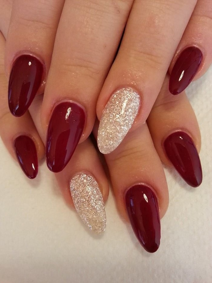 classic red nail polish, worn on two pale hands, with oval shaped nails, resting on a white surface, the ring finger nails are decorated with fine silver glitter