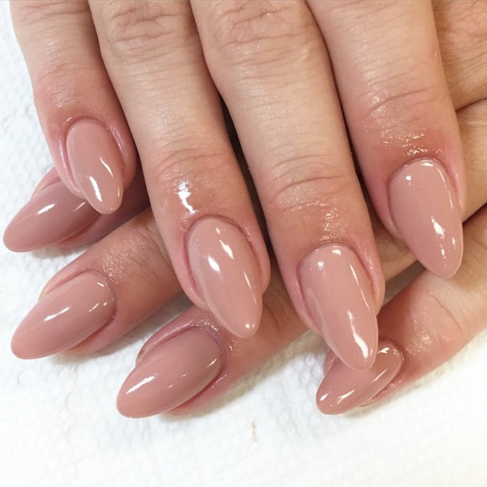 eight fingers with almond-shaped manicure, with smooth and glossy, nude pink nail polish, short pointy nails