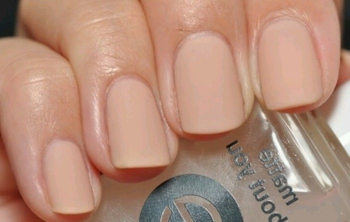 manicure with short square nails, painted in a nude pink nail polish, seen in close up, on a hand holding a clear bottle of nail polish