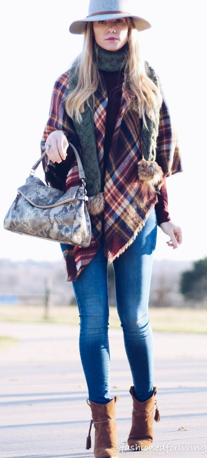medium blue skinny jeans, worn with brown suede ankle boots, a black jumper, and two sets of scarves, by a blonde woman, in a pale grey felt hat