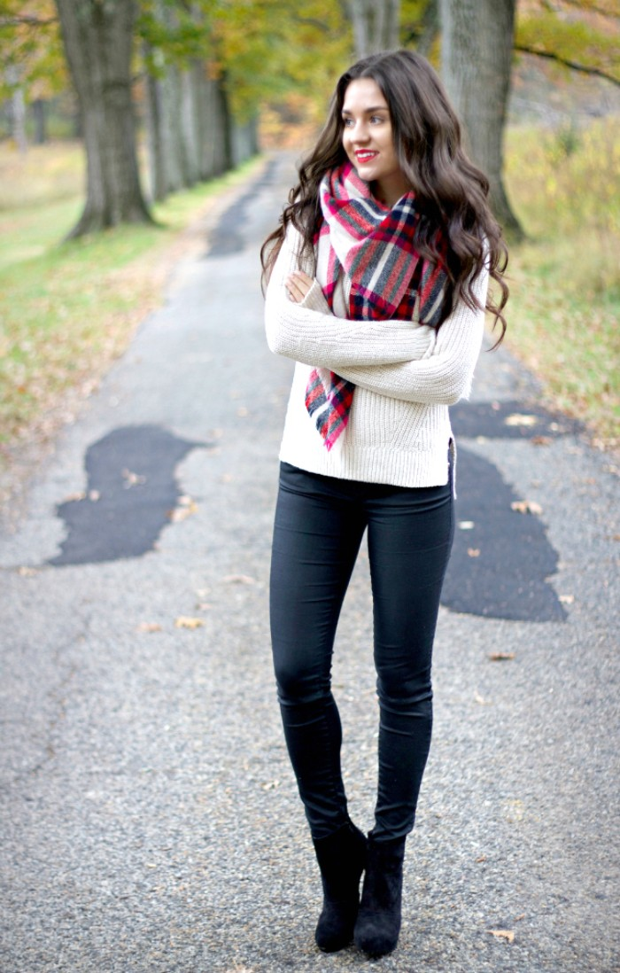 knitted sweater in white, worn with black skinny trousers, black high heeled ankle boots, and a large plaid scarf, by a smiling brunette woman