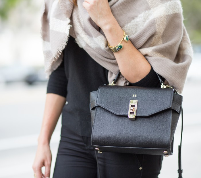 arm bag made from black leather, worn by a woman, dressed in black, with a creamy grey oversized shawl, featuring off-white patterns, draped around her shoulders, how to fold a blanket scarf, seen in close up